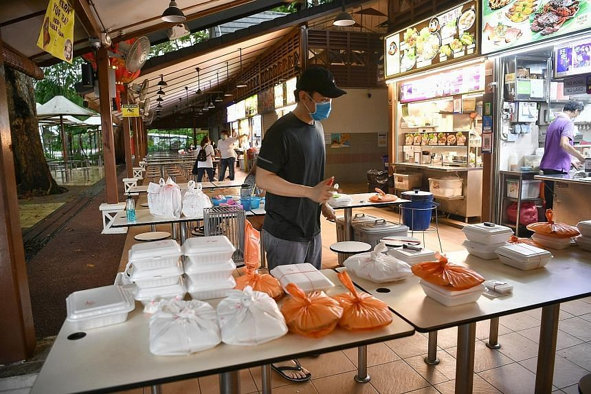 Mr Kelvin Foo, the owner of Hai Yan BBQ Seafood, managing delivery orders on Friday. The stall, at Newton Food Centre, uses four tables to split up the deliveries bound for different locations. This way, delivery personnel are kept at least 1m apart
