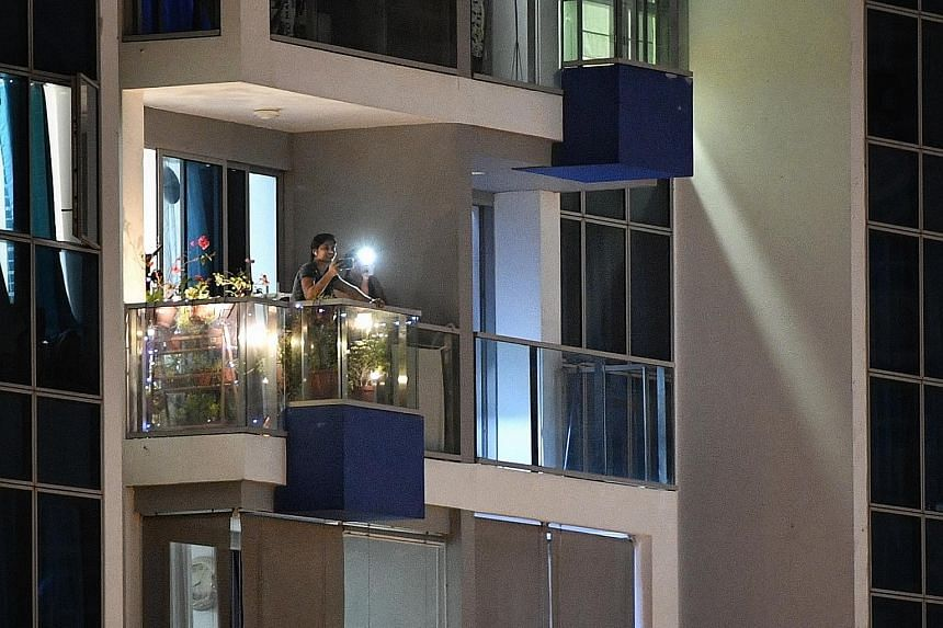 A car parked along Tampines Street 86 for its occupants to join in the islandwide singalong yesterday evening. Residents from Tampines GreenForest singing along to Home and flashing lights from their cellphones at 7.55pm yesterday. A resident at SkyV