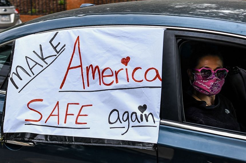 A demonstrator in a drive-by protest in the United States on Friday, amid lockdowns in several states in the country to try to curb the pandemic. A poll released this month showed a drop in President Donald Trump's approval rating. Another poll fou