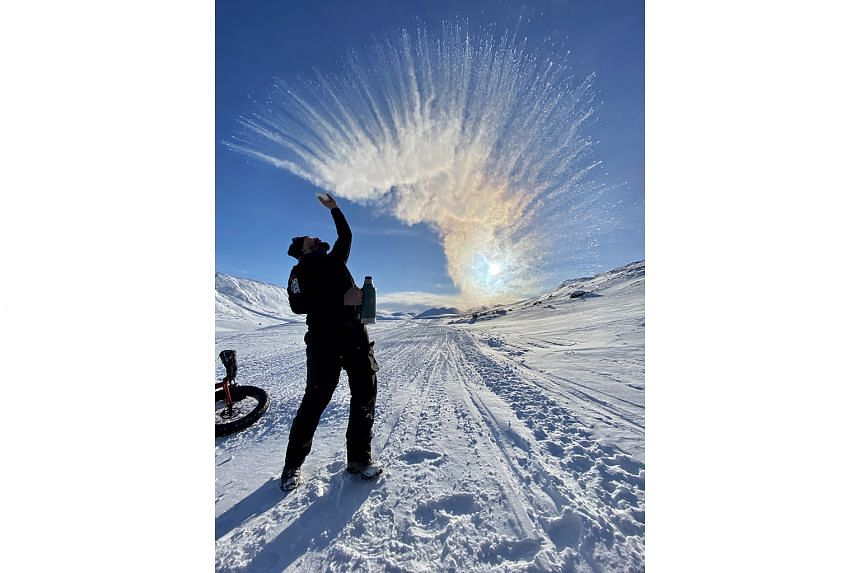 A team member throws hot water in the air to show how fast it turns to ice vapour.