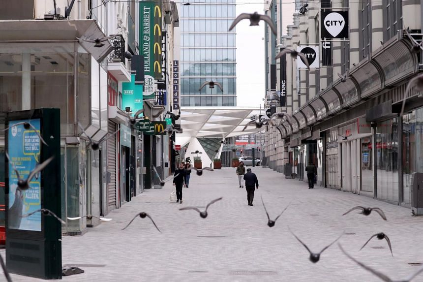 People walk along an almost empty shopping street in Brussels, Belgium, on March 20, 2020.