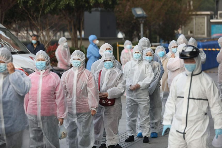 Patients who recovered from the coronavirus wear protective clothing as they line up to be tested again at a hospital in Wuhan, on March 14, 2020.