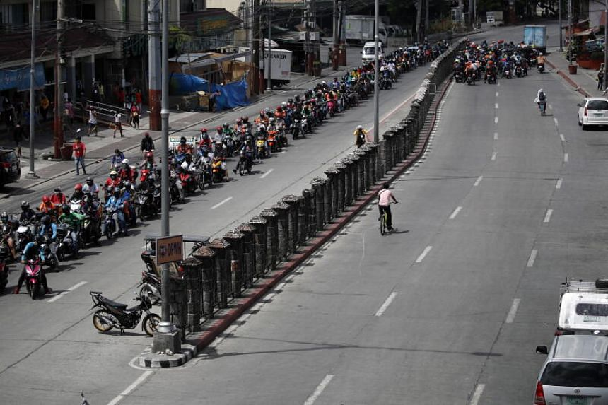 Motorcyclists queue at a quarantine checkpoint in Bacoor, Philippines, on April 17, 2020.