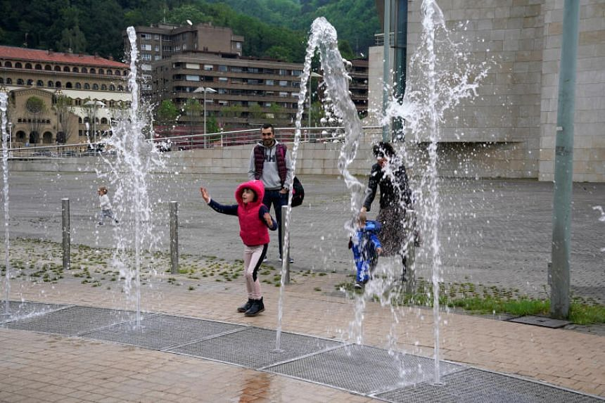 A child plays in a fountain in Bilbao, Spain, on April 26, 2020.