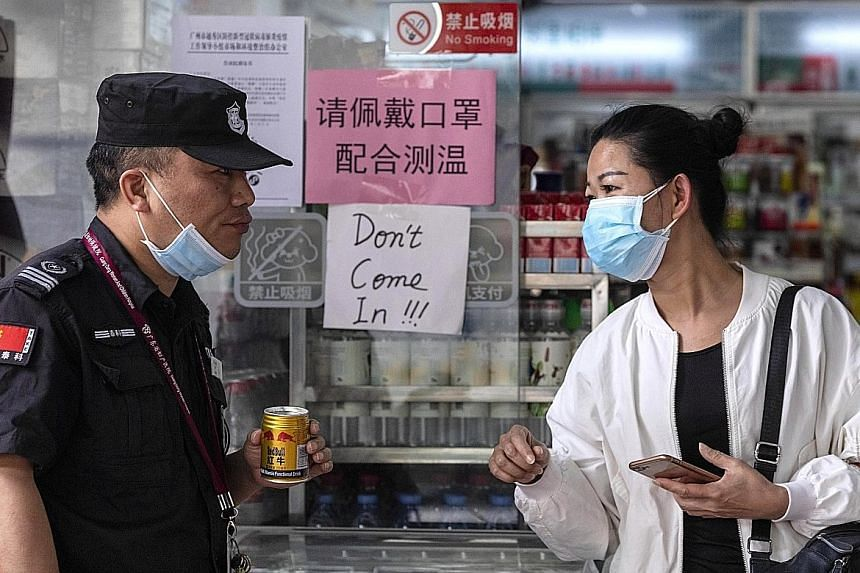 """A woman speaking to a guard outside a shop with a sign in Chinese saying people must wear a mask to enter, next to a sign in English that says """"Don't come in!!!"""" in an area popular with the African community in Guangzhou."""