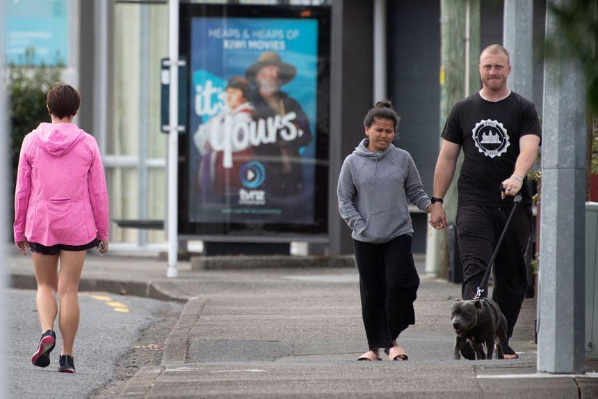 Pedestrians practise social distancing along a street of Lower Hutt, near Wellington, on April 20, 2020.