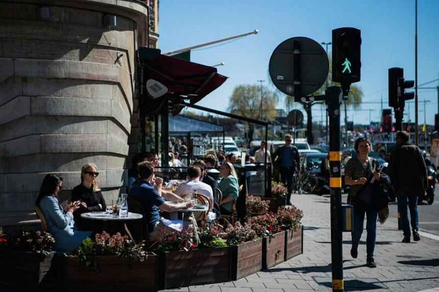 Stockholmers soaking up the spring sunshine outside a restaurant on April 22, 2020.
