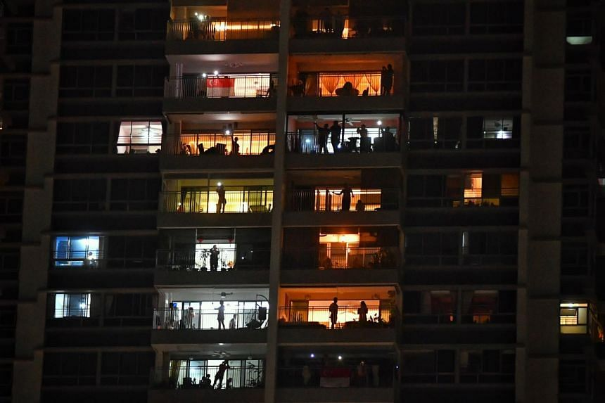 Residents cheer and shine lights from their balconies at The Peak @ Toa Payoh on April 25, 2020.