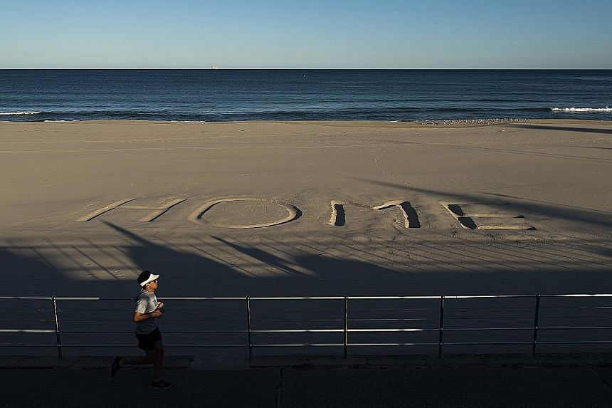 A message written in the sand on Australia's Bondi Beach urging people to stay home. Canberra last week said it would push for an international probe into the coronavirus pandemic at the World Health Assembly next month. Commuters, all with face mask