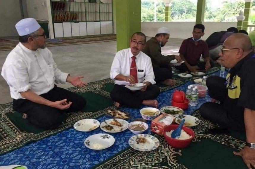 Deputy minister Noor Azmi Ghazali (centre) having a meal at an Islamic school in Perak on April 18.