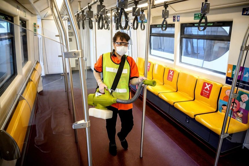 An employee sprays disinfectant in a BTS commuter train carriage in Bangkok on April 28, 2020.