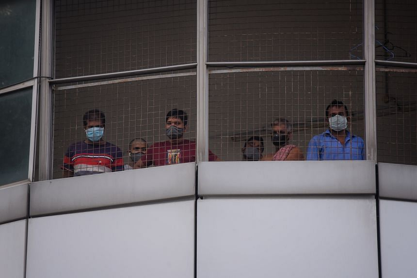Migrant workers peek out of a fence at a factory-converted dormitory in Tuas on April 25, 2020.