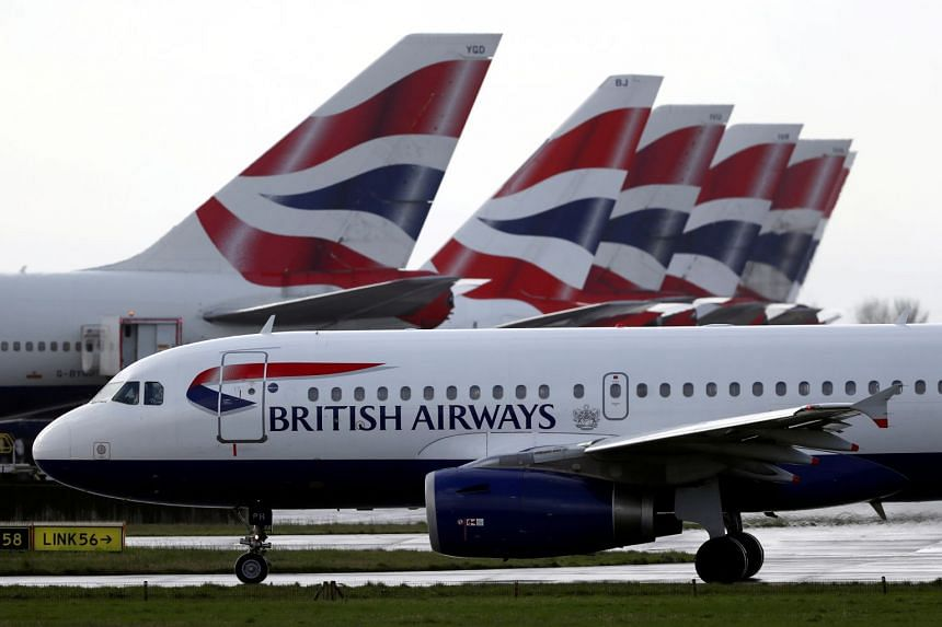 A British Airways plane taxis past the tail fins of parked aircraft at Heathrow Airport in London.