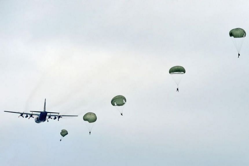 In a photo taken on May 14, 2013, a string of parachutes blooms behind a C-130 Hercules.
