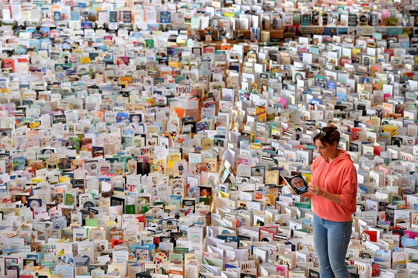 Mandy Alison poses with a selection of over 125,000 cards sent to Captain Tom Moore, displayed in the Great Hall of Bedford School, on April 28, 2020.