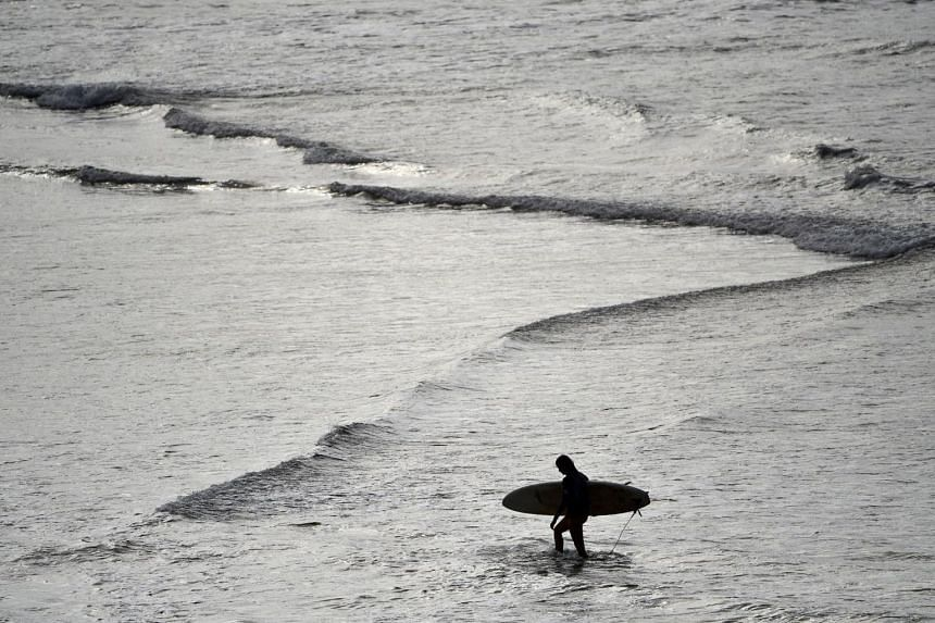 A surfer carries his board in the ocean at Bondi Beach on April 28, 2020.