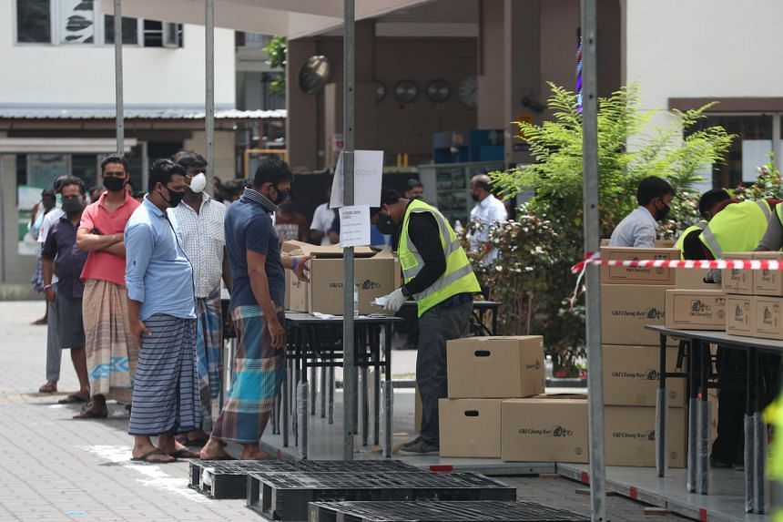 Migrant workers queue to collect food on April 18, 2020. They are residents of Jurong Penjuru Dormitory 1.