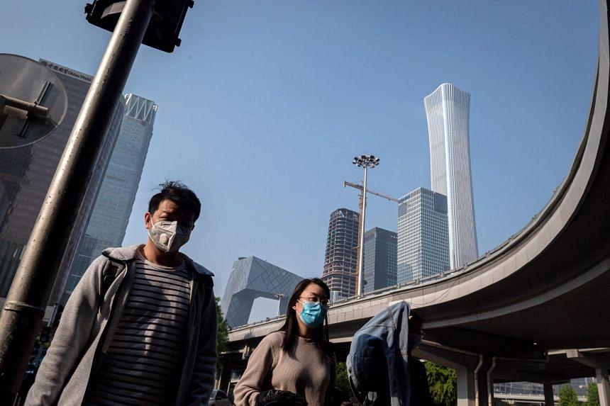 People wearing masks walk on a street in Beijing, on April 28, 2020.