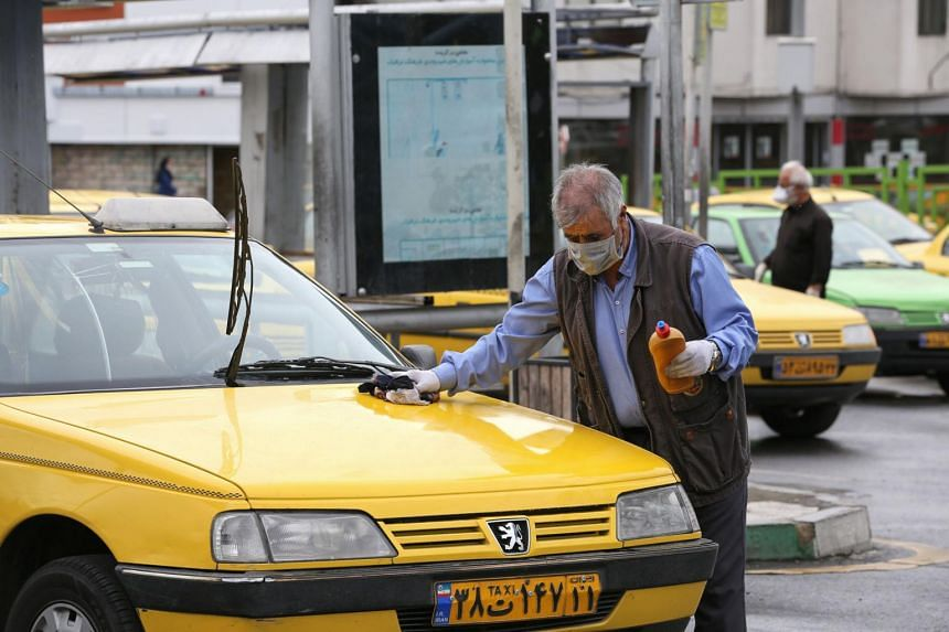 A taxi driver cleans his car while waiting for passengers at Aryashahr station, west Teheran on April 26, 2020.