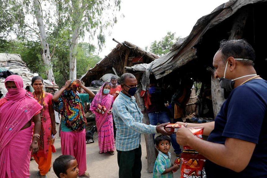 A man distributes food to residents living in a slum in New Delhi on April 29, 2020.