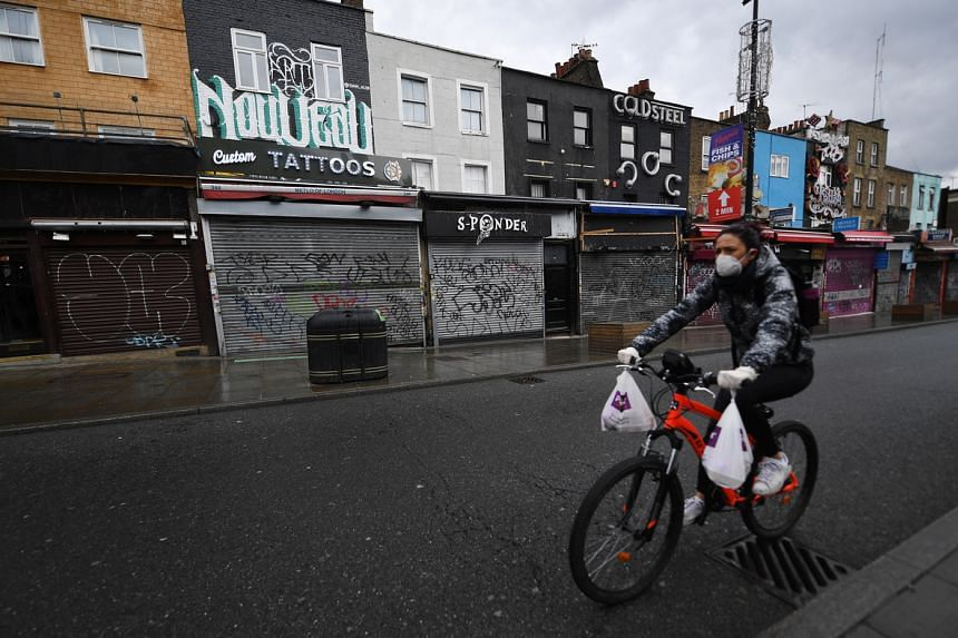 A cyclist rides past the closed shutters of Camden High Street in London, on April 29, 2020.