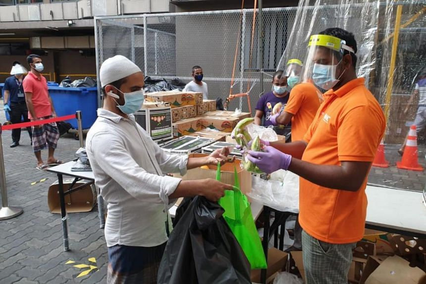 Migrant workers at Westlite Toh Guan dormitory receiving bananas donated by Sumifru Singapore.