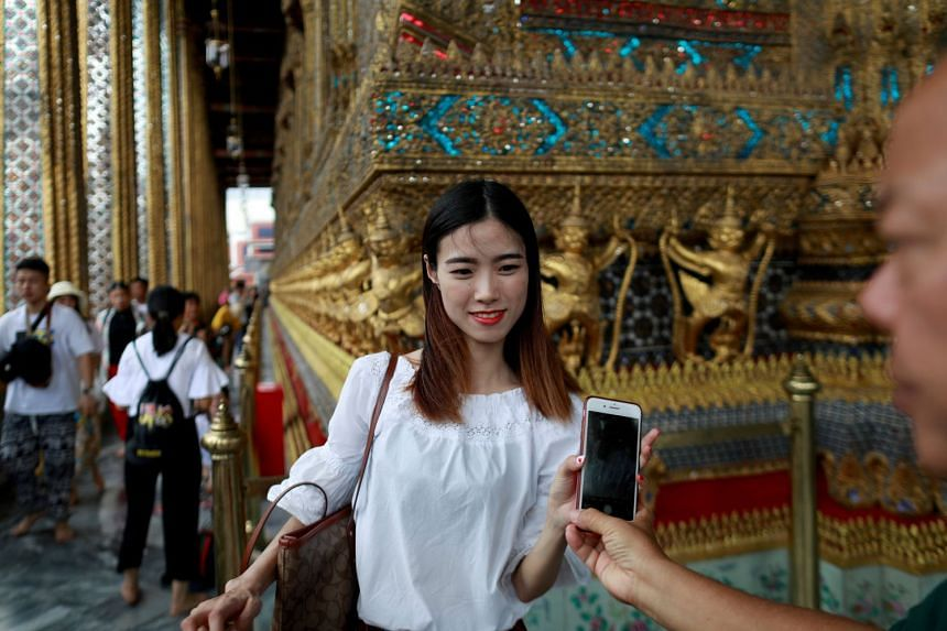 Chinese tourists visit the Temple of the Emerald Buddha in Bangkok, Thailand, in August 2018.
