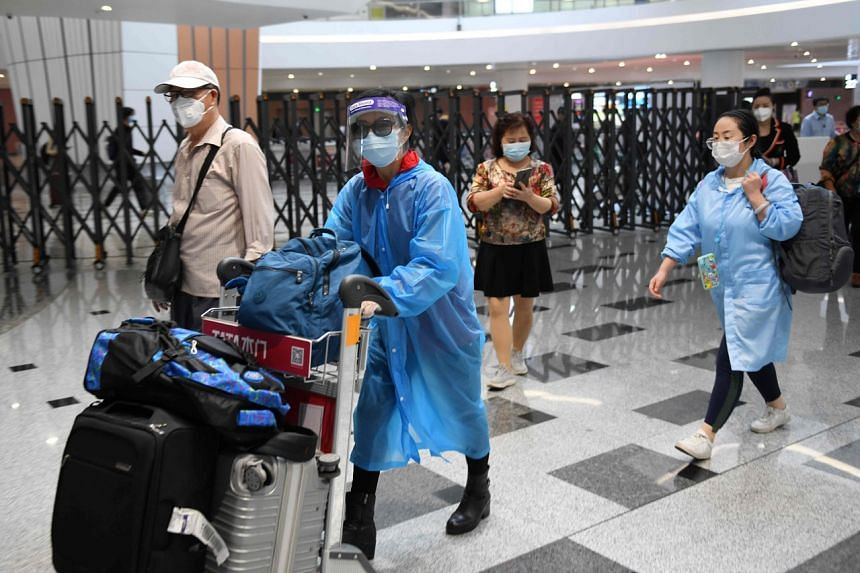 Travellers wear face masks as they arrive at Beijing Daxing Airport on April 30, 2020.