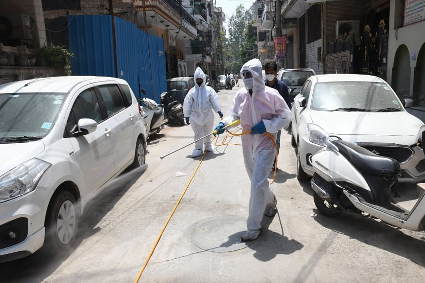Workers spray disinfectant at residential areas in North Delhi, May 1, 2020.