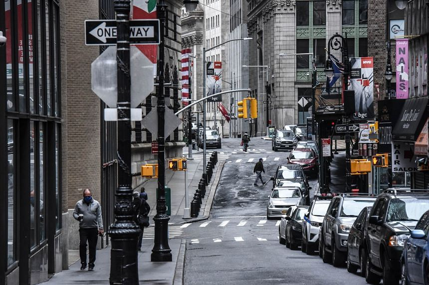 An empty street and closed businesses are seen in New York City's financial district.