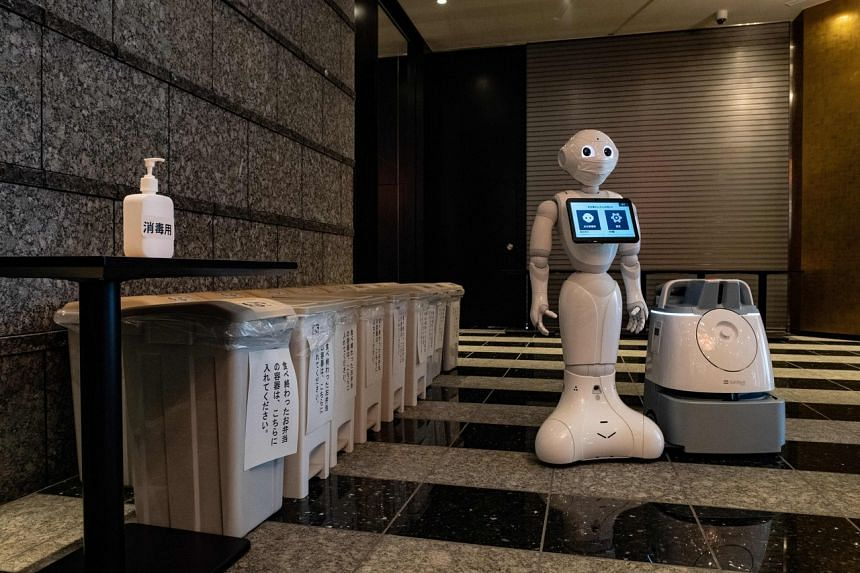 The Pepper greeting robot stands with a cleaning robot at a hotel lobby in Tokyo on May 1, 2020.