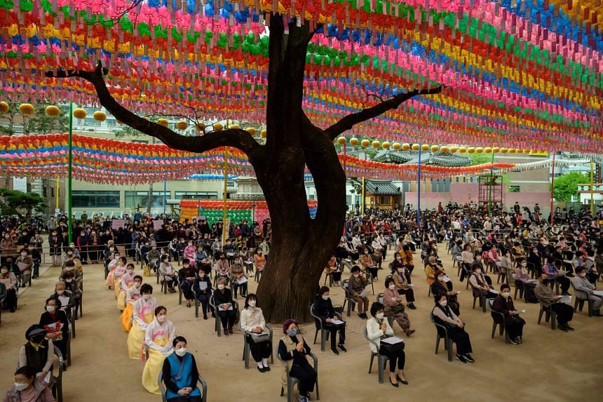 """Worshippers wearing face masks attending a prayer ceremony entitled """"Overcoming and healing the Covid-19 coronavirus"""", while marking Buddha's birthday at the Jogye Buddhist Temple in Seoul yesterday. South Korea's success in containing the outbreak -"""