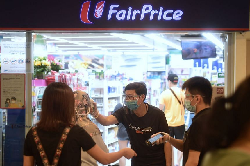 Shoppers having their temperatures checked and NRICs scanned at the FairPrice outlet in Toa Payoh yesterday to facilitate contact tracing.