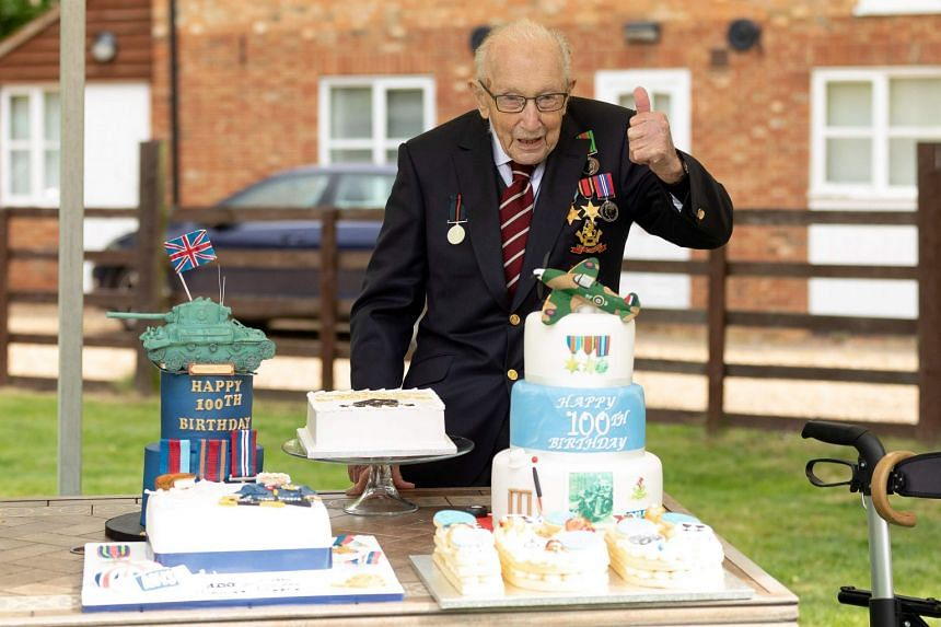Tom Moore poses with cakes to celebrate his 100th birthday in the village of Marston Moretaine.