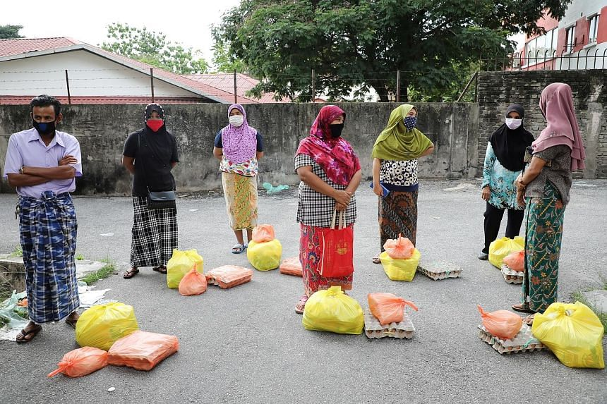 Rohingya refugees in protective masks keeping a safe distance while waiting to receive goods from volunteers, during the ongoing movement control order, in Kuala Lumpur early last month. Malaysia had opened up its borders in 2017 to provide temporary