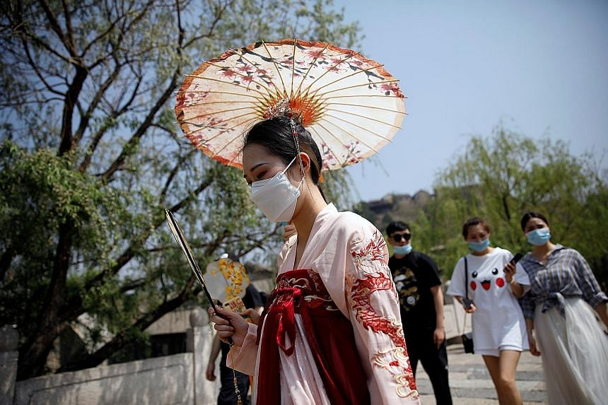 A visitor to Gubei Water Town yesterday wearing a face mask and traditional Chinese clothing. The town, 110km from Beijing, normally teems with tourists on Labour Day, but crowds were thin yesterday. PHOTO: REUTERS