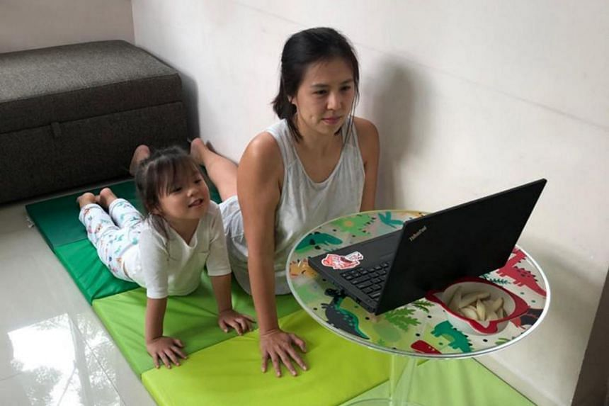 DBS Bank vice-president of group strategic marketing and communications Michelle Tan participating in a virtual pilates session with her four-year-old daughter.