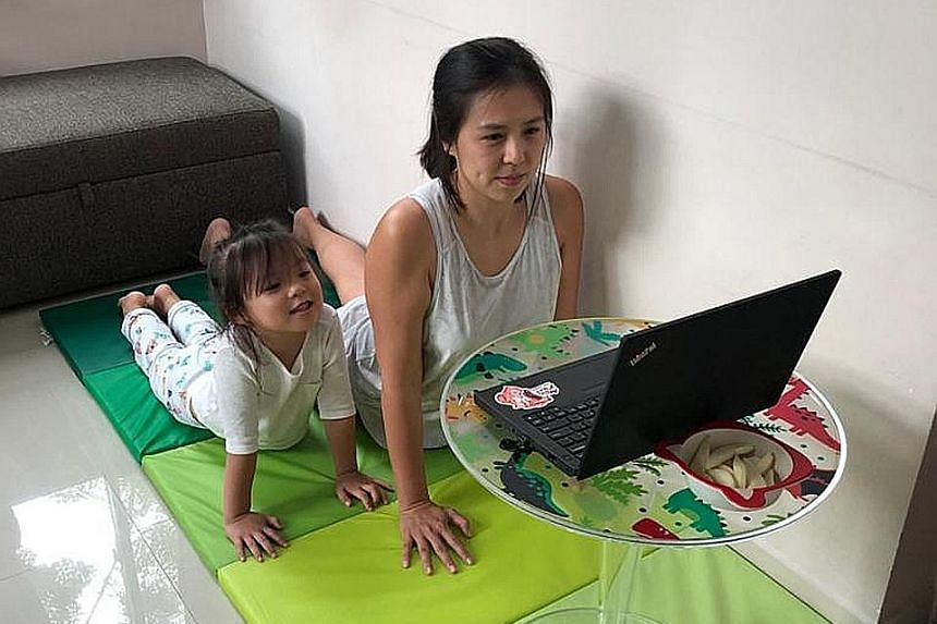 Ms Michelle Tan, DBS Bank vice-president of group strategic marketing and communications, participating in a virtual yoga session for staff with her four-year-old daughter.