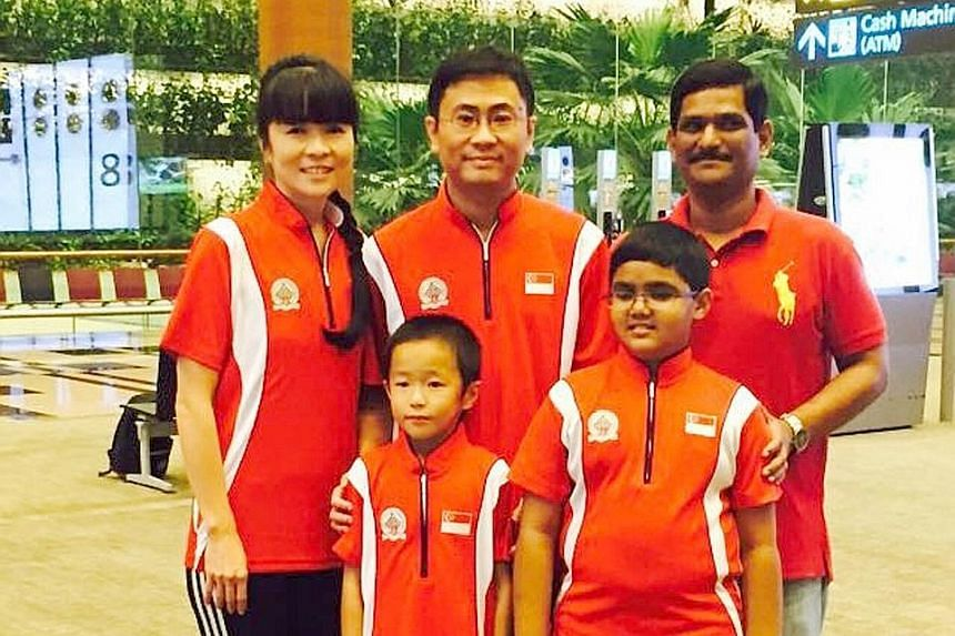 Above: Goh Zi Han, 11, is a candidate master of chess despite his tender age, and has played the game in 16 nations. Below: Singapore chess wunderkinds Zi Han and Siddharth Jagadeesh, 13, with their respective parents (back row, from left) Lo Li Wen