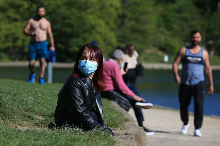 A woman enjoys the sunshine in Roundhay Park in Leeds, northern England, on May 2, 2020.