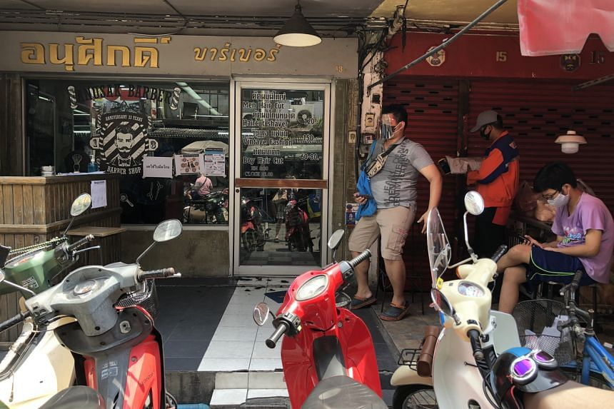 A queue outside a barbershop in Bangkok on May 3, 2020.