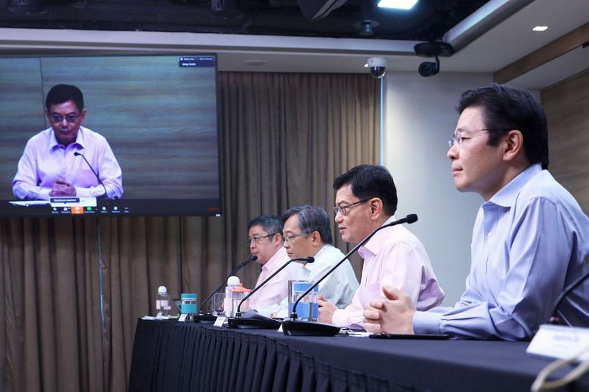 Below: Workers at S11 Dormitory. A fourth wave emerged around March 30 when foreign workers started coming down with the virus. Right: Deputy Prime Minister Heng Swee Keat joining a virtual press conference by the multi-ministry task force on April 2