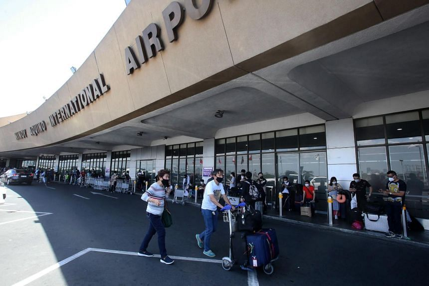 In a photo from March 19, 2020, passengers queue outside Manila's international airport.