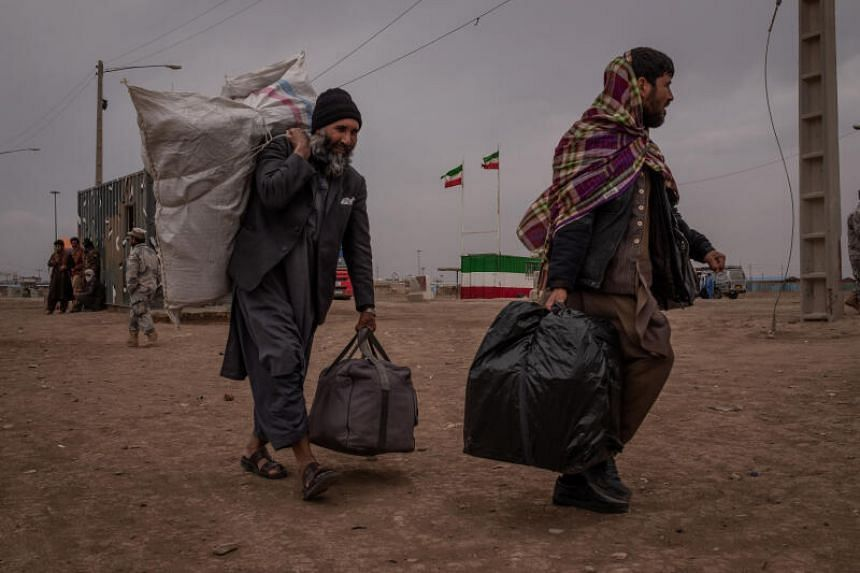 A photo taken on March 22, 2020, shows Afghans returning from Iran at the Islam Qala border crossing.