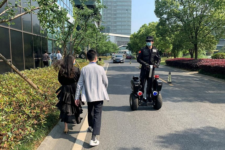 """Equipped with an infrared sensor and a camera, the glasses measure temperatures on the move, allowing the wearer to """"see"""" people's temperatures. A security guard wearing thermal glasses developed by Chinese start-up Rokid patrolling on a scooter, ami"""