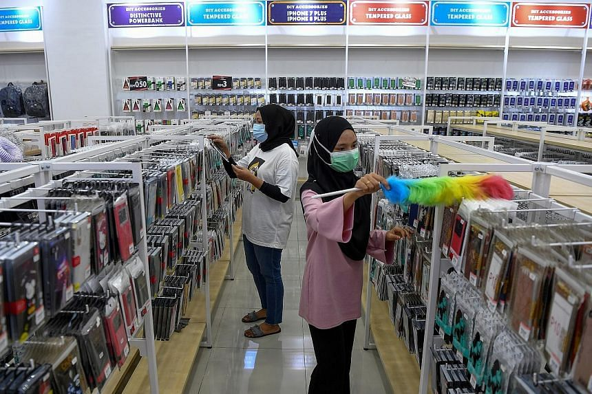 Workers at a mobile phone accessories shop in Terengganu preparing yesterday to resume business today. Under rules announced last Friday, most businesses in Malaysia will be allowed to reopen, while people can return to work and begin dining at resta