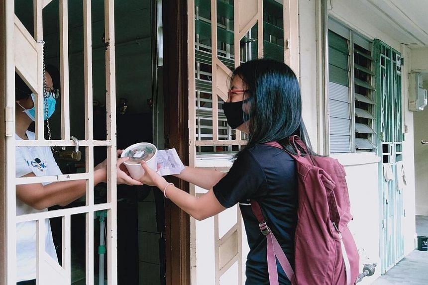 Miss Lim Si Hui, senior lead of outreach and partnerships at Glyph, delivering a meal from Knead to Eat to a resident in Bukit Merah.