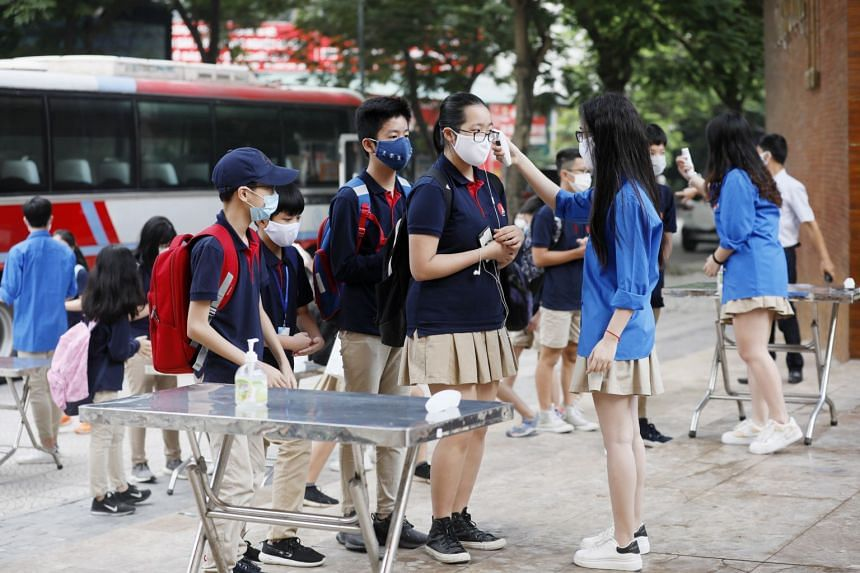 Students having their temperatures checked at a school in Hanoi on May 4, 2020.