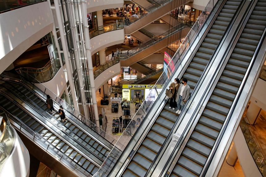 A couple wearing protective face masks ride an escalator at a shopping mall in Seoul, South Korea, on April 8, 2020.