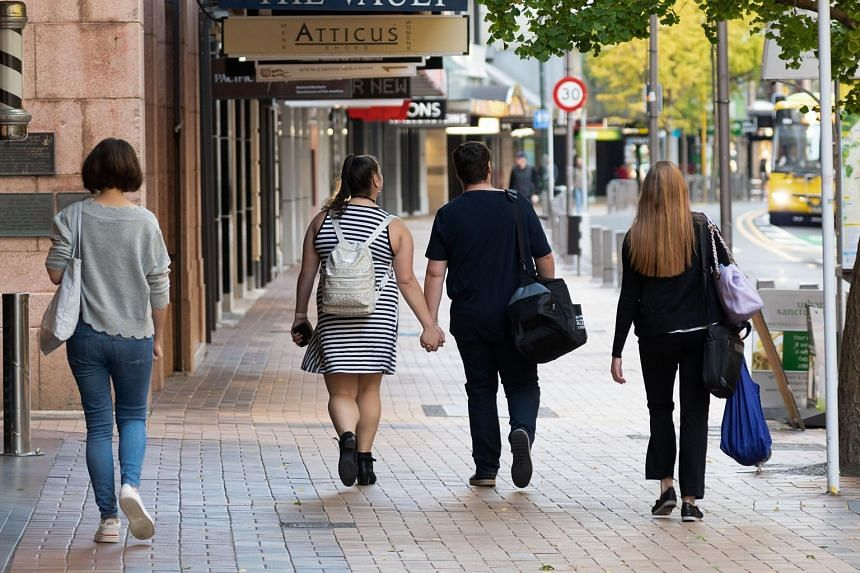 People walk down a street on the first day of the easing of restrictions in Wellington, on April 28, 2020.